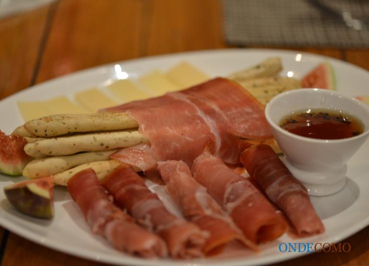 Grissini trufado (pão tipo italiano em forma de palito, crocante com gergelim, parma, lascas de grana padano, Figo e mel trufado.