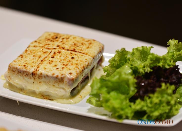 Croque Monsieur (sanduíche recheado com queijo Emmenthal e presunto, com cobertura gratinada de queijo, acompanha mix de folhas)