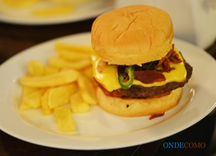 Scrumburguer (pão de hambúrguer, hambúrguer, queijo prato, bacon, onion rings, barbecue e pimenta jalapeño)
