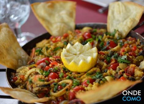 Paella bucanera (paella de marisco, tierra ou mestiza, en arroz español com granos de bico y pimientas de bico, uvas passas blancas, alcaparras, huevos de codorniz y cheiro verde)