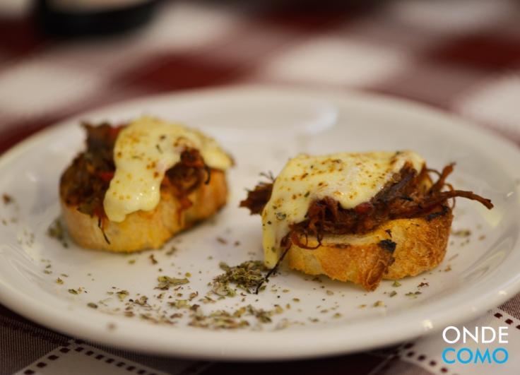 Bruschetta de ragu de carne seca com queijo canastra
